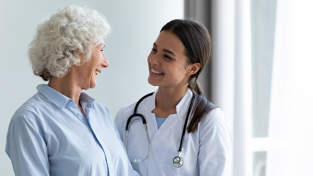 Smiling_Caring_Young_Female_Nurse_Doctor_Caretaker_Assisting_Happy_Senior_Impact_Transition